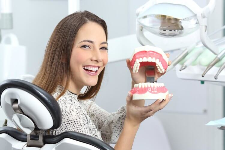 Morgan Street Dental Centre Gum Disease Family Dentistry- Woman with Beautiful Smile Showing Model Teeth